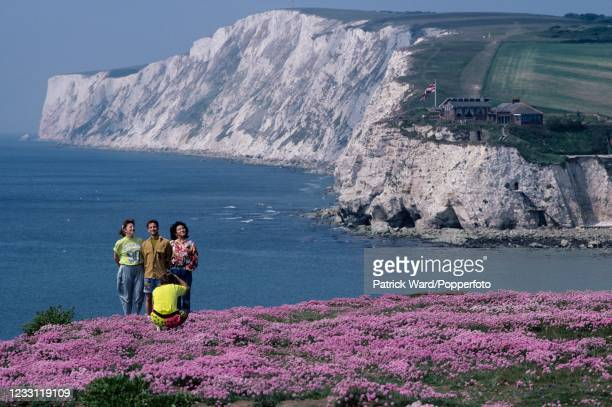 Tourists posing for photographs at Freshwater Bay, with chalk cliffs beyond, on the Isle of Wight, circa August 1996.