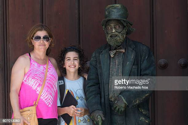 Tourists posing for picture next to living statue in Old Havana