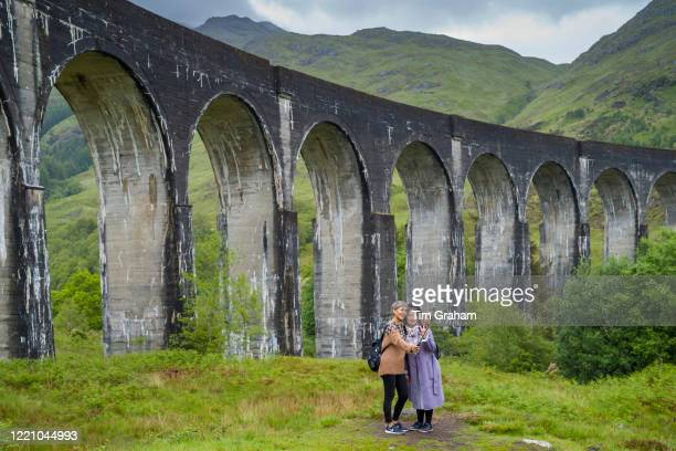 Tourists posing for selfies at famous Glenfinnan Viaduct tourist spot in the Highlands of Scotland.