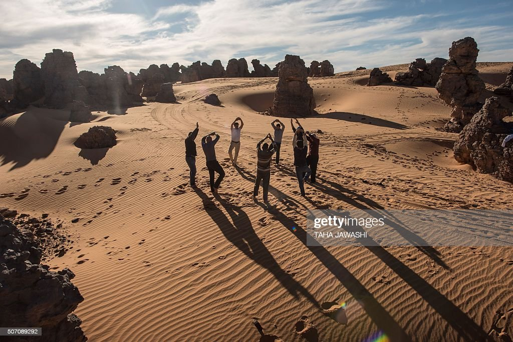 Tourists practice yoga in the Meggedat valley, north west of Libya's Akakus mountain region, in the desert of the western Ghat District, on January 2, 2016. JAWASHI