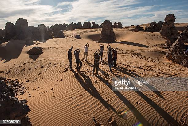 Tourists practice yoga in the Meggedat valley north west of Libya's Akakus mountain region in the desert of the western Ghat District on January 2...