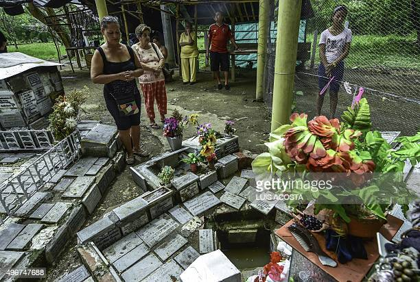 Tourists pray before the tomb of child Omaira Sanchez killed in the disaster in the town of Armero Tolima department Colombia on November 5 2015...