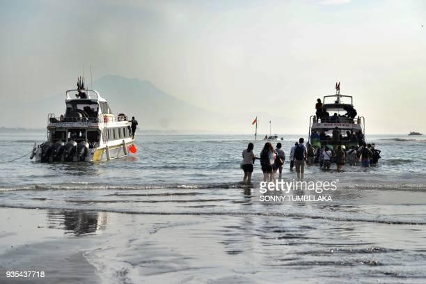Tourists prepare to board boats to Nusa Penida island from Sanur beach on Bali on March 21, 2018. / AFP PHOTO / SONNY TUMBELAKA