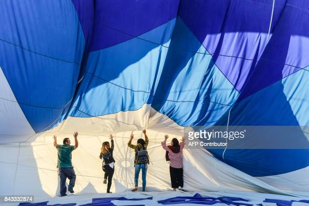 Tourists prepare to take off with a hot air balloon for a flight over Nevsehir in Turkey's historical Cappadocia region Central Anatolia eastern...