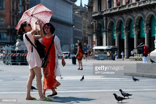 Tourists protect themselves from the sun with an umbrella on June 22, 2017 at Piazza Duomo in Milan during a hot summer-day. In Italy, forecasters...