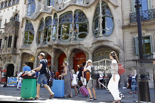 Tourists pull their suitcases in front of Spanish architect Gaudi's Casa Batllo in Barcelona on June 28 2015 Tourists generated 14% of municipal GDP...