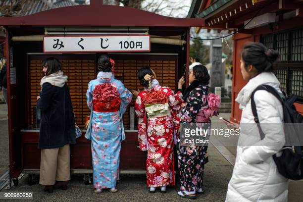 Tourists purchase 'omikuji' fortunetelling paper strips as they visit Sensoji buddhist temple on January 19 2018 in Tokyo Japan Sensoji is Tokyo's...