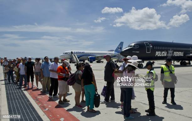 Tourists queue before boarding planes at the airport of San Jose del Cabo on September 16 2014 a day after hurricane Odile which has since been...