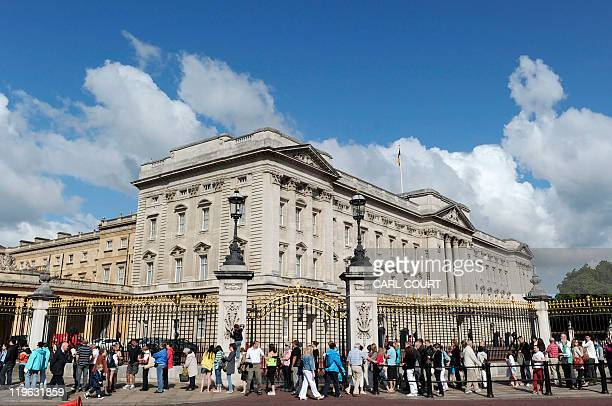 Tourists queue outside Buckingham Palace in central London as the palace opens its doors to the public for the summer on July 23 to showcase...