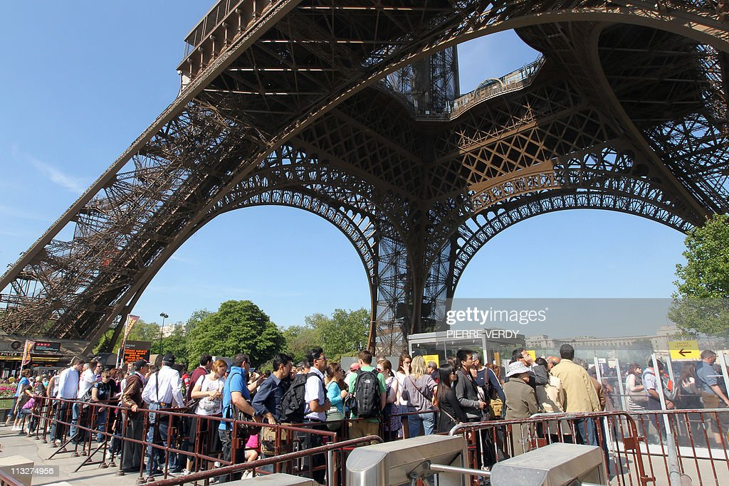 Tourists queue outside the Eiffel Tower : News Photo