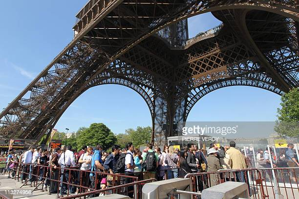 Tourists queue outside the Eiffel Tower on April 21 2011 in Paris Designed by Gustave Eiffel and built in 1889 for the International Exhibition of...