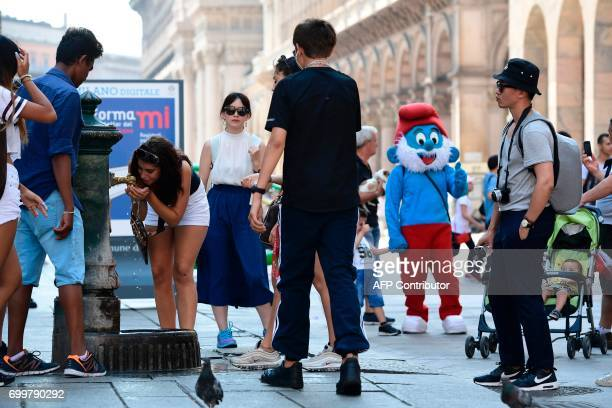 Tourists queue to drink water at a public fountain on June 22, 2017 at Piazza Duomo in Milan during a hot summer-day. In Italy, forecasters say the...