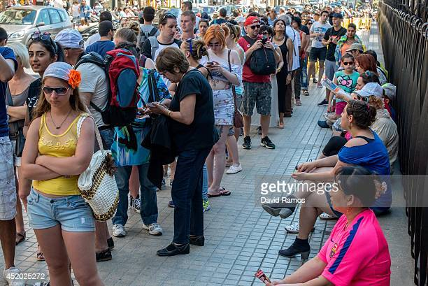 Tourists queue to get in La Sagrada Familia on July 11 2014 in Barcelona Spain As traders of 'La Boqueria' complain about tour groups getting in the...
