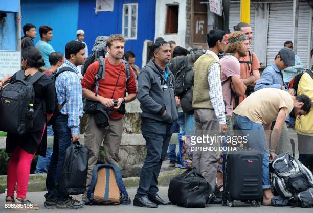 Tourists queue to leave amid clashes between Indian security personnel and protesters and an indefinte strike called by the Gorkha Janmukti Morcha in...