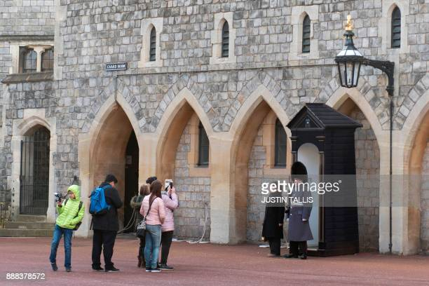 Tourists queue to take photos with a solider on guard duty inside the grounds of Windsor Castle in Windsor west of London on December 8 2017...