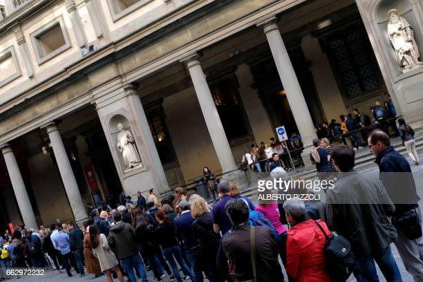 Tourists queue to visit the Uffizi gallery one of the most important Italian museum on April 1 2017 in Florence / AFP PHOTO / Alberto PIZZOLI