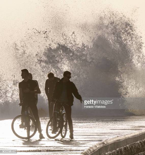 Tourists react at being drenched by large waves braking into one of the wave breakers during the last day of the year in Tamariz Beach on December 31...