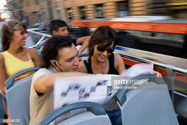 tourists reading map atop double-decker bus - double decker bus stock pictures, royalty-free photos & images