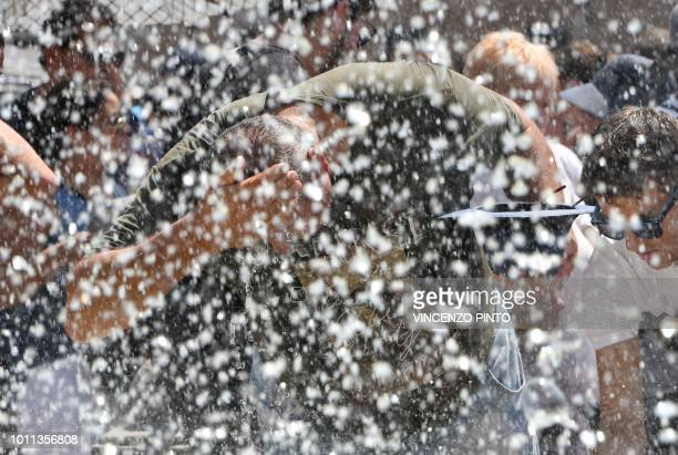 Tourists refresh themselves at a fountain in St Peter's Square at the Vatican prior to Pope Franci's Sunday Angelus prayer on August 5 2018