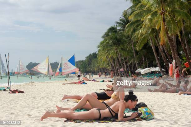 Tourists relax along a beach in Boracay island in Malay town Aklan province central Philippines on April 7 2018 The Philippine tourism industry...