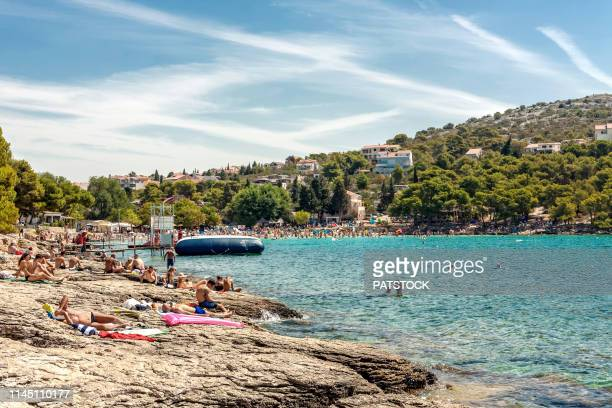 tourists relaxing on rocky beach of slanica bay. in the background there is a famous sandy beach. - kroatien stock-fotos und bilder