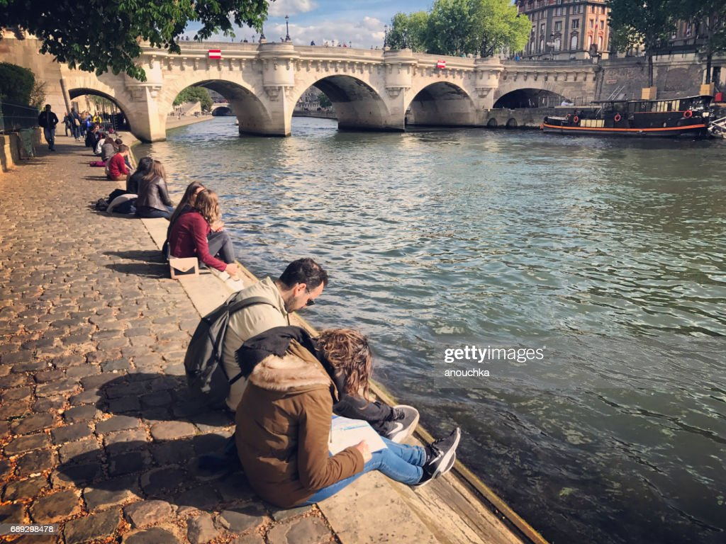 Tourists relaxing on Seine Riverbank, Paris, France : Stock Photo