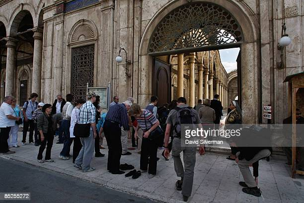 Tourists remove their shoes before entering the 19th century Ottomanera Muhammad 'Ali mosque an alabaster covered landmark which dominates the...
