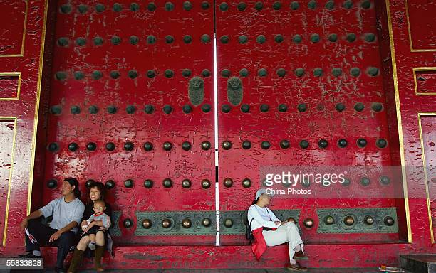 Tourists rest in front of a palace gate in the Forbidden City on September 26 2005 in Beijing China The Forbidden City first built in 1406 also known...