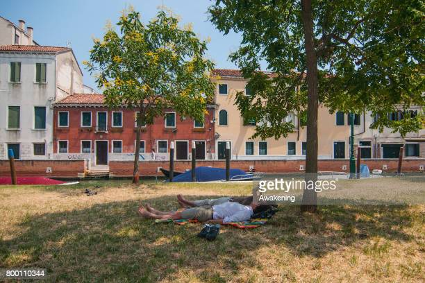 Tourists rest in the shade of a tree for protection from the sun and heat on July 23 2017 in Venice Italy An intense heatwave is sweeping across many...