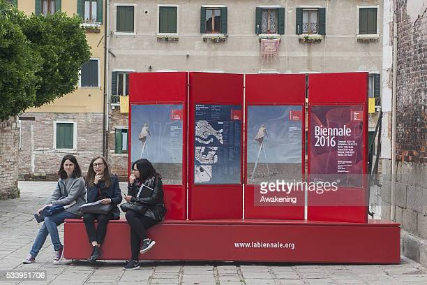 Tourists rest on a street sign of the 15th Architecture Venice BiennaleNear the Arsenale area on May 24 2016 in Venice Italy The 56th International...