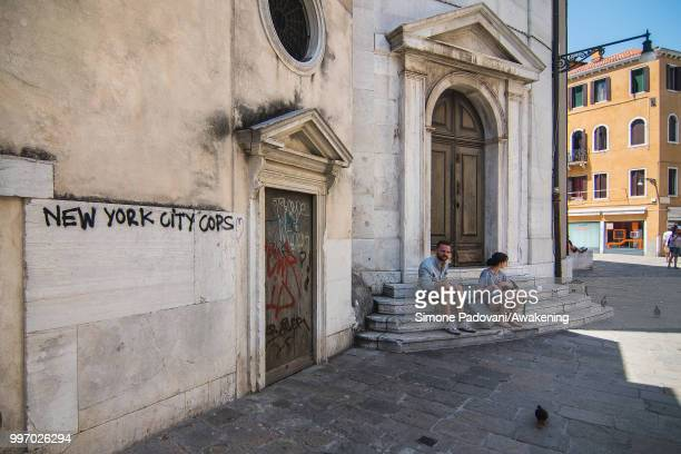 Tourists rest on the stairs of the church of Santa Maria Maddalena where there are graffiti and tags on the walls on the way that connects Railway...