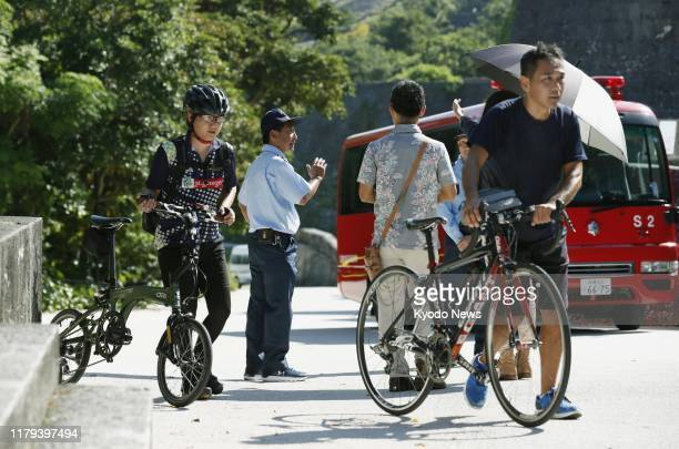 Tourists return as Shuri Castle is closed in Naha Okinawa Prefecture southern Japan on Nov 2 after a predawn fire two days ago engulfed the buildings...