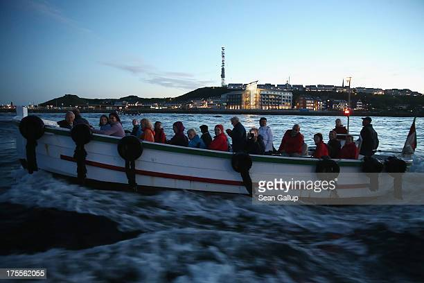 Tourists return from an evening excursion as Helgoland town is visible behind on August 3 2013 at Heligoland Island Germany Heligoland Island in...