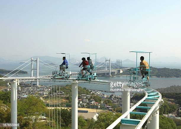 Tourists ride a pedal-powered sky cycle roller coaster at Washuzan Highland Amusement Park on April 27, 2013 in Kurashiki, Japan. Washuzan Highland...