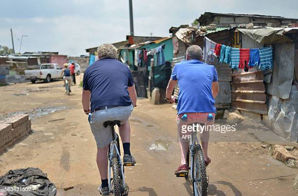 Tourists ride bicycle in Alexandra township Johannesburg on February 12 2013 Muludzi Tours offers the opportunity to discover one of the oldest and...