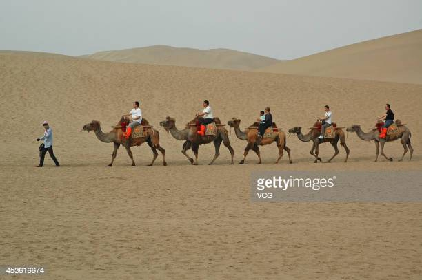 Tourists ride camels along sand dunes on the Silk Road on May 21 2012 in Dunhuang China 'The Silk Road' was adopted into the World Heritage List on...