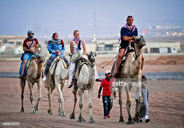 Tourists ride camels in Egypt's Red Sea resort of Sharm ElSheikh on November 4 2015 Britain temporarily suspended flights from Sharm ElSheikh as it...