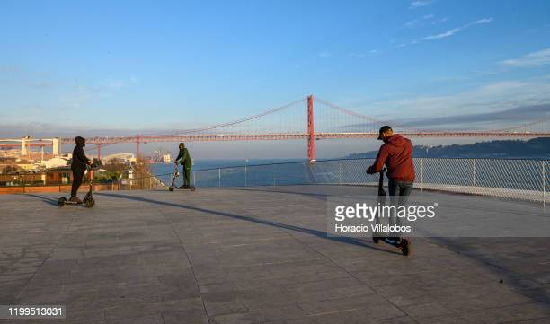 Tourists ride escooters at MAAT museum terrace by the Tagus River on January 13 2020 in Lisbon Portugal Since their introduction in Lisbon escooters...