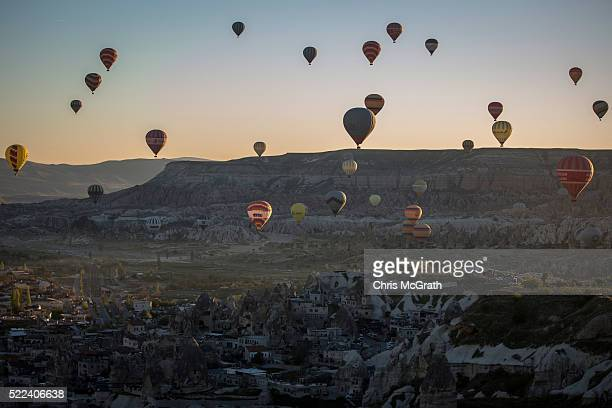 Tourists ride hot air balloon near the town of Goreme on April 17 2016 in Nevsehir Turkey Cappadocia a historical region in Central Anatolia dating...