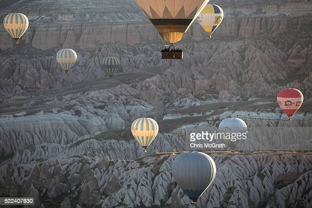 Tourists ride hot air balloons near the town of Goreme on April 17 2016 in Nevsehir Turkey Cappadocia a historical region in Central Anatolia dating...