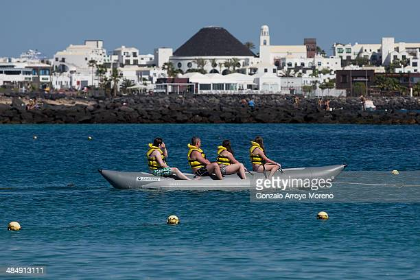 Tourists ride on a raft at at Playa Blanca beach on April 13 2014 in Lanzarote Spain Lanzarote where British Prime Minister David Cameron and his...