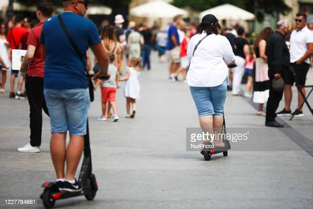 Tourists ride on electric scooters at the Main Square, popular tourist destination, during coronavirus pandemic. Krakow, Poland on July 26, 2020....