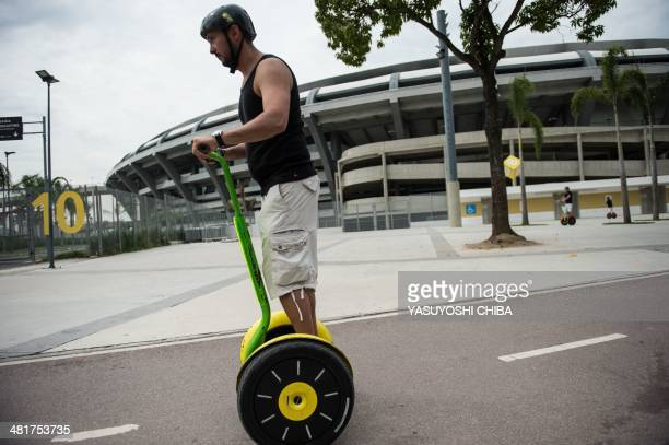 Tourists ride on the electric transport called Segway in front of Maracana stadium in Rio de Janeiro Brazil on March 31 2014 AFP PHOTO / YASUYOSHI...