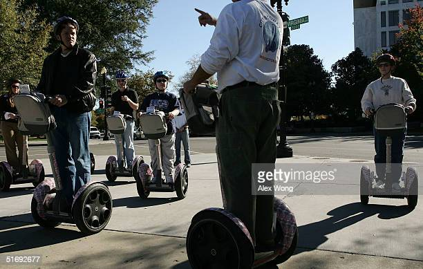 Tourists ride the Segway Human Transporters as they listen to their tour guide during a Segway tour November 6, 2004 in Washington, DC. Tourists can...