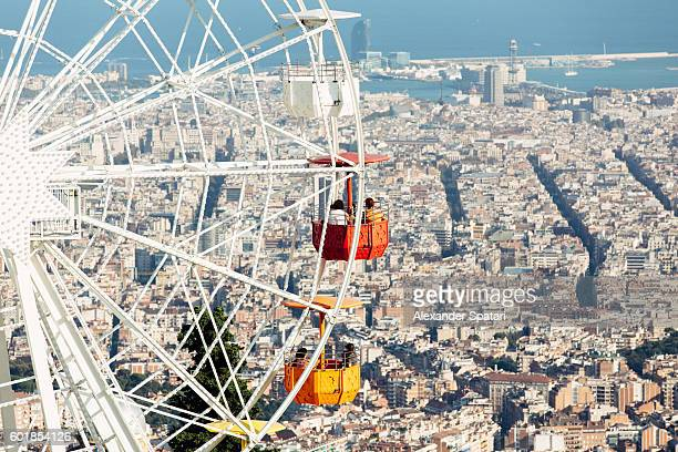 Tourists riding a ferris wheel at the amusement park at Tibidabo mountain in Barcelona, Catalonia, Spain