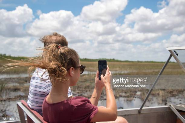 Tourists riding airboat and taking photos of nature in the Everglades The Everglades is a natural region of tropical wetlands in the southern portion...