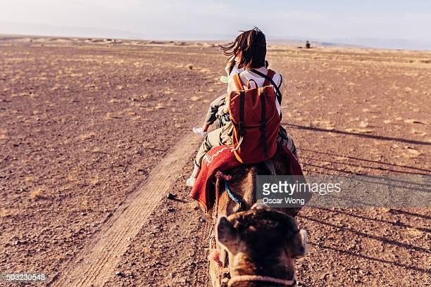 Tourists riding camels through the desert