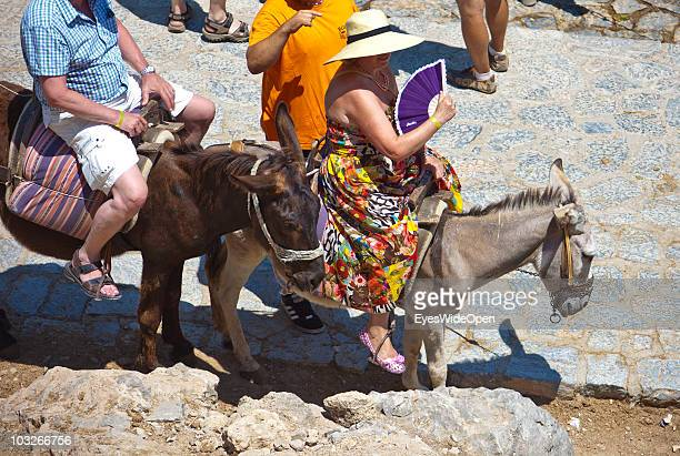 Tourists riding donkeys up to the Acropolis of Lindos on July 04 2010 in Lindos Greece The old town of Lindos is famous for its class listed...