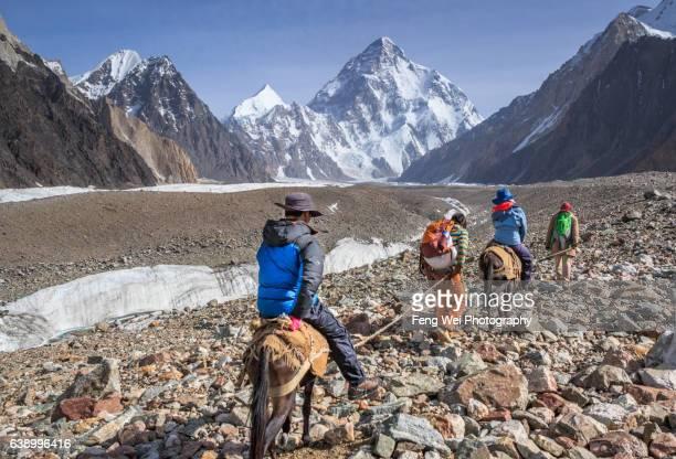 tourists riding horse from concordia to k2 base camp, central karakoram national park, gilgit-baltistan, pakistan - k2 mountain stock pictures, royalty-free photos & images