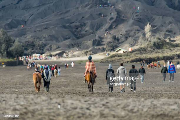 tourists riding horse up to bromo volcano crater - bromo crater stock pictures, royalty-free photos & images